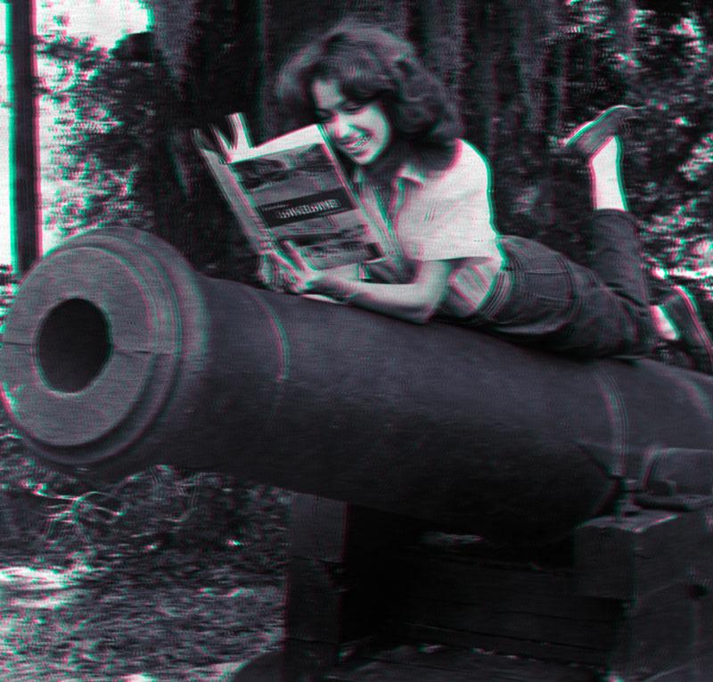Une jeune fille lit allongée sur un canon militaire.